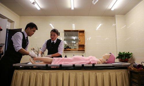 Technicy w zakładzie pogrzebowym w Babaoshan używają plastikowego manekina, aby zademonstrować sposób mycia zmarłego.